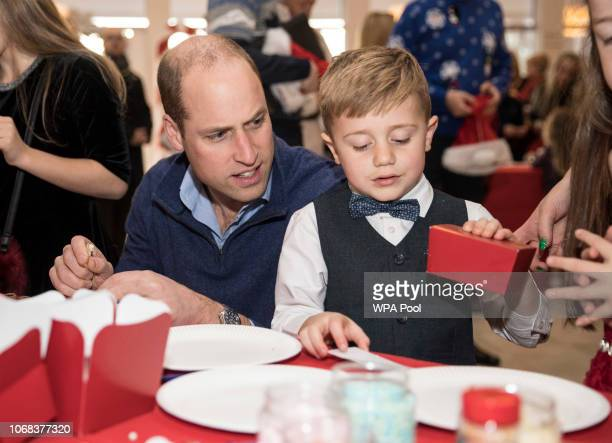 Prince William Duke of Cambridge sits with Spencer Best aged 5 years as they make chocolate truffles as he takes part in a children's pretend snow...