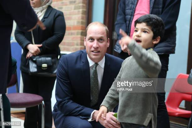 Prince William Duke of Cambridge speaks to a young boy at the AlManaar Muslim Cultural Heritage centre during a visit to Support4Grenfell community...