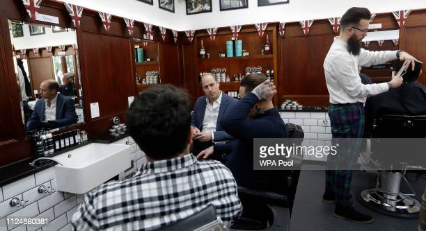 Prince William Duke of Cambridge speaks to Dean Hamilton and Paul Richardson as he visits the Pall Mall Barbers on February 14 2018 in London England...