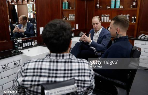 Prince William Duke of Cambridge speaks to to Dean Hamilton and Paul Richardson as he visits Pall Mall Barbers on February 14 2018 in London England...