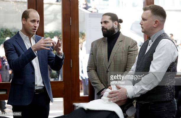 Prince William Duke of Cambridge speaks to Tom Chapman founder of the charity and barber Daniel Davies during a visit to Pall Mall Barbers on...