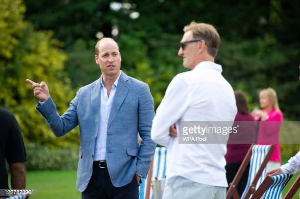 Prince William Duke of Cambridge speaks with former Arsenal player Tony Adams as he hosts an outdoor screening of the Heads Up FA Cup final on the...