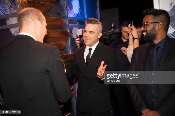 Prince William Duke of Cambridge speaks with Robbie Williams and Romesh Ranganathan as they attend the Royal Variety Performance at Palladium Theatre...