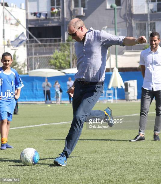 Prince William Duke of Cambridge takes a penalty kick as he visits a footballbased youth programme operated by The Equaliser a social sport...