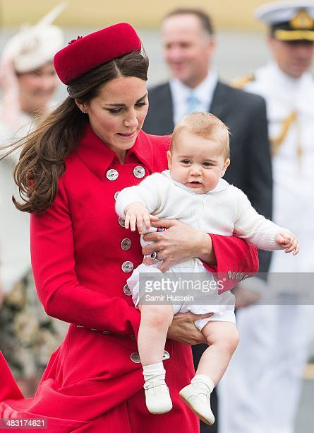Prince William Duke of Cambridge touches the leg of Prince George of Cambridge with Catherine Duchess of Cambridge as they arrive at Wellington...