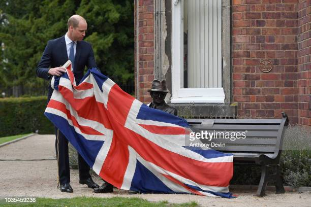 Prince William Duke of Cambridge speaks with Michael Mamelock and views his emigration papers as he meets families of those helped by Major Frank...