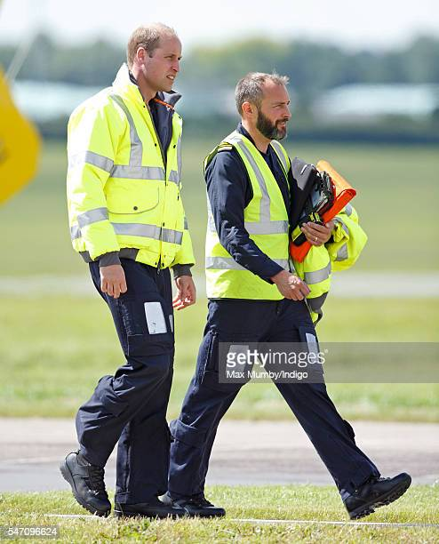 Prince William Duke of Cambridge walks across the helipad after piloting his air ambulance into land at the East Anglian Air Ambulance base at...