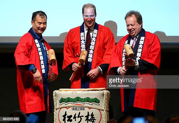 Prince William Duke of Cambridge waves dressed in a 'Happi' coat takes part in a Sake Barrell Breaking Ceremony with Japanese Astronaut Soichi...
