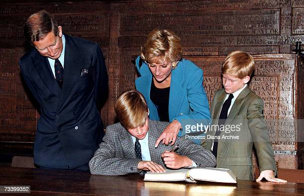 Prince William follows Eton tradition by signing a book before starting at the school as Prince Charles Princess Diana and Prince Harry look on...
