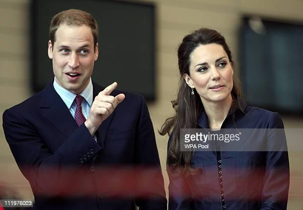 Prince William gestures alongside fiancee Kate Middleton during a visit to Darwen Aldridge Community Academy on April 11 2011 in Darwen northwest...