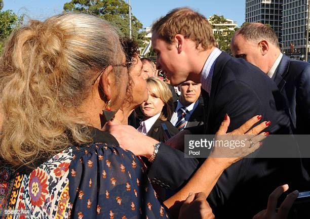 Prince William is given a kiss on the cheek as he meets with members of the local Redfern aboriginal community during a visit to the Redfern...