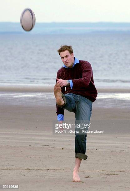 Prince William Laughing And In A Happy Mood Kicking A Rugby Football On The Sandy Beach Near His University Home Looking Relaxed And Casual Barefoot...