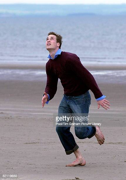 Prince William Looking Up To Catch A Football He Has Kicked Into The Air On The Sandy Beach Near His University Home. Looking Relaxed And Casual In...
