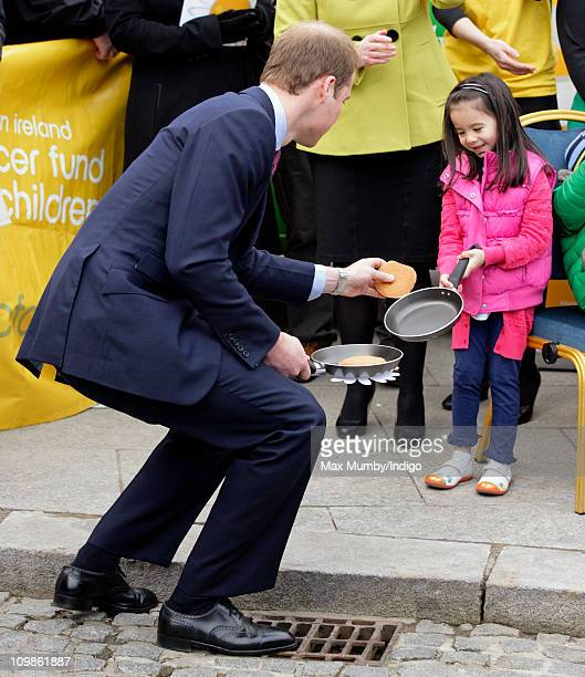 Prince William picks up a young girl's pancake after she dropped it whilst practising her pancake tossing during a visit to City Hall on March 8 2011...