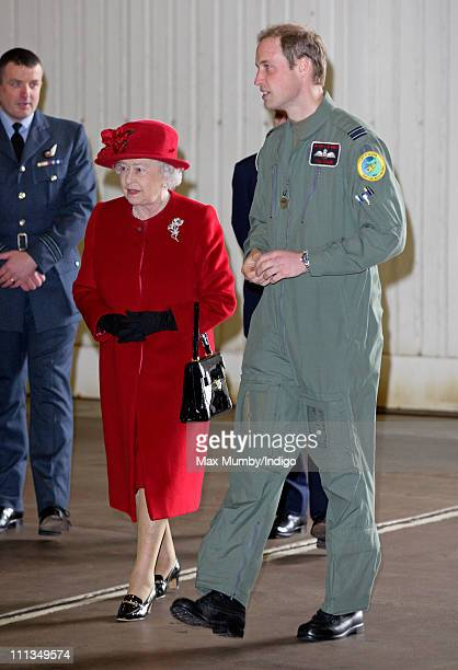Prince William shows his grandmother Queen Elizabeth II around a Sea King search and rescue helicopter as she visits RAF Valley where Prince William...