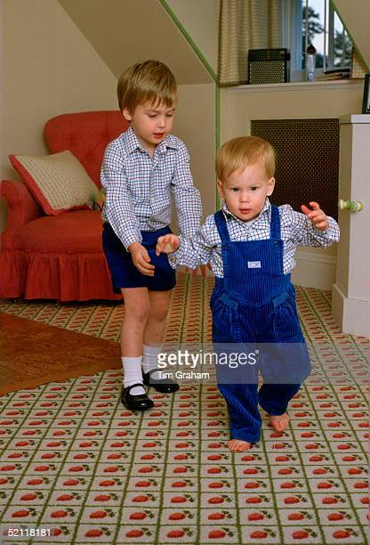 Prince William Standing Behind His Brother, Prince Harry, To Help Him As He Tries To Walk On His Own In The Playroom At Kensington Palace