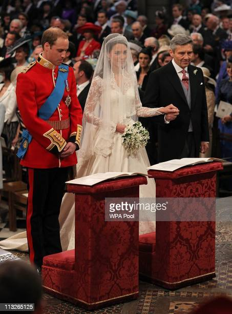 Prince William stands beside his bride Catherine Middleton as she holds the hand of her father Michael Middleton on April 29 2011 in London England...