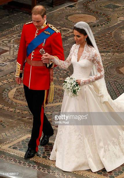 Prince William takes the hand of his bride Catherine Middleton now to be known as Catherine Duchess of Cambridge as they walk down the aisle inside...