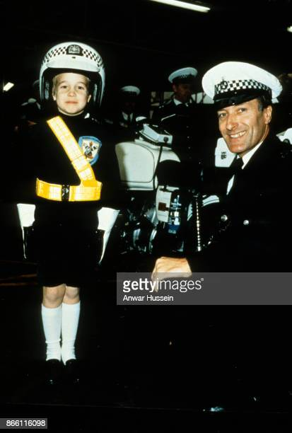 Prince William wearing a police helmet stands to attention during a visit to s police station on November 30 1987 in Windsor England