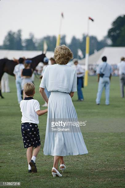 Prince William with his mother Diana Princess of Wales with their backs to the camera attending the Cartier International Polo Day held at Smiths...