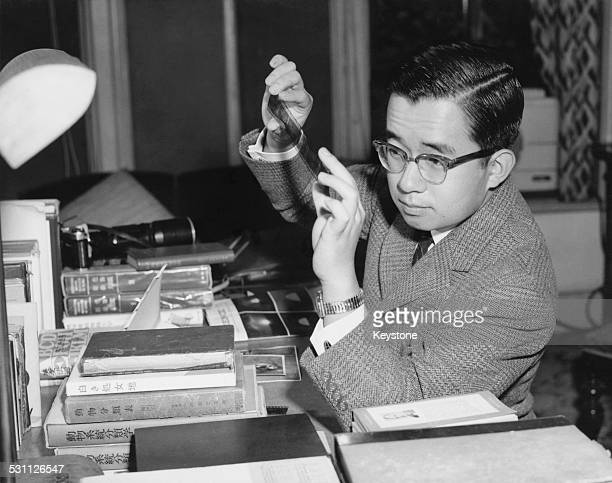 Prince Yoshi later Masahito Prince Hitachi the second son of Emperor Hirohito of Japan examines his negatives after photographing birds in the...