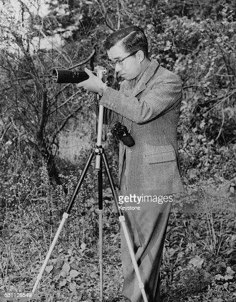 Prince Yoshi, later Masahito, Prince Hitachi, the second son of Emperor Hirohito of Japan, using a camera fitted with a telephoto lens in the gardens...