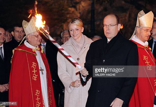 Prince's Albert II of Monaco and princess Charlene arrive with torches on January 26 2012 in Monaco to take part in the SainteDevote procession...