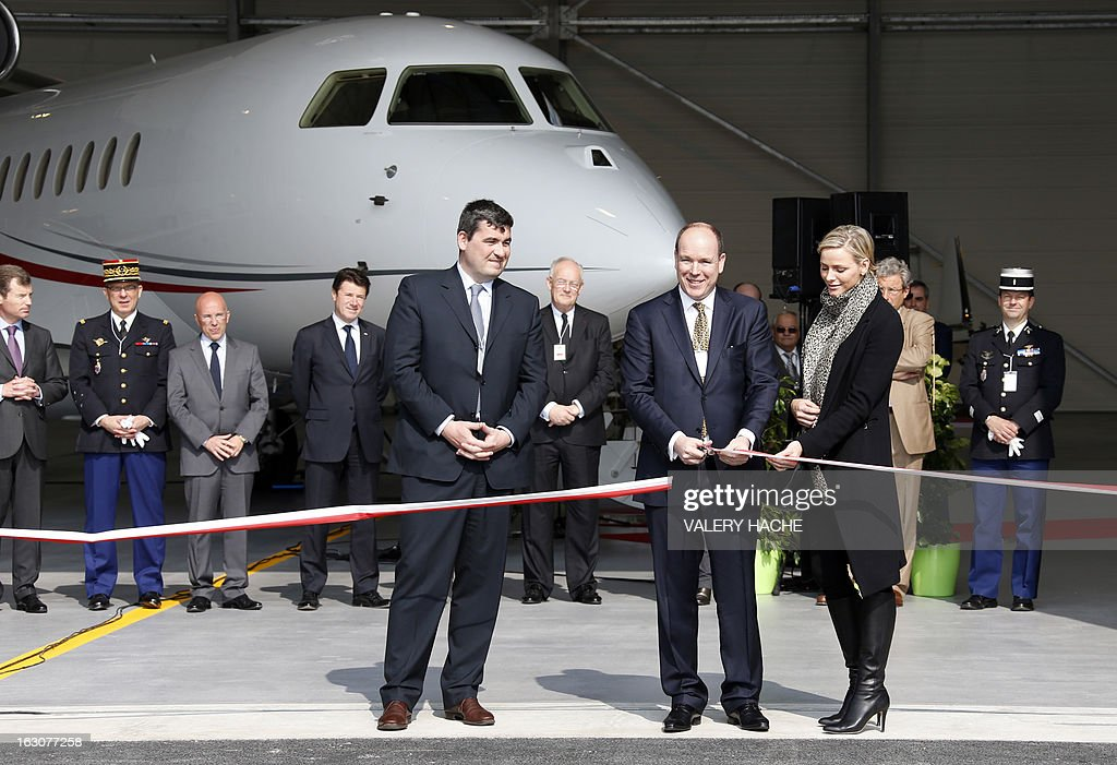 Prince's Albert II of Monaco (C) cuts the ribbon on March 4, 2013 next to his wife Princess Charlene as they attend the presentation of the Monegasque Princely family's new 'Falcon 7X' plane and its hangar in Nice airport, southeastern France.