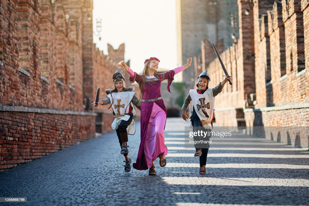 Princes and her knights running through castle courtyard : Stock Photo