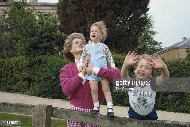 Princes William and Harry with their mother, Diana, Princess of Wales in the garden of Highgrove House in Gloucestershire, 18th July 1986. William is...