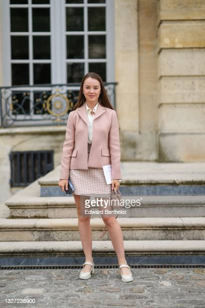 Princess Alexandra of Hanover wears gold earrings, a gold necklace, a white shirt, a pale pink blazer jacket, a pale pink and white houndstooth...