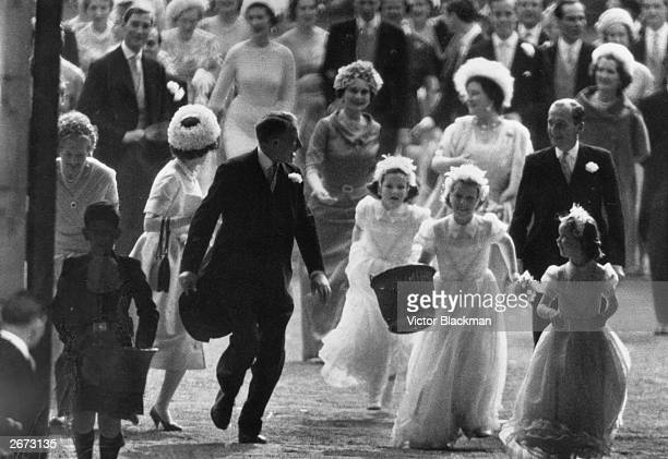 Princess Anne carrying a confetti basket leads the other bridesmaids at the wedding of her aunt Princess Margaret On the left is Prince Charles with...