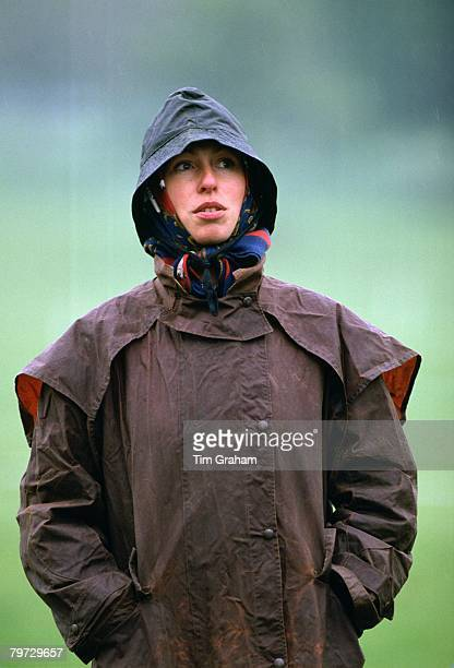Princess Anne dressed in a Barbour style coat and waterproof hat in the rain at Windsor Horse Trials