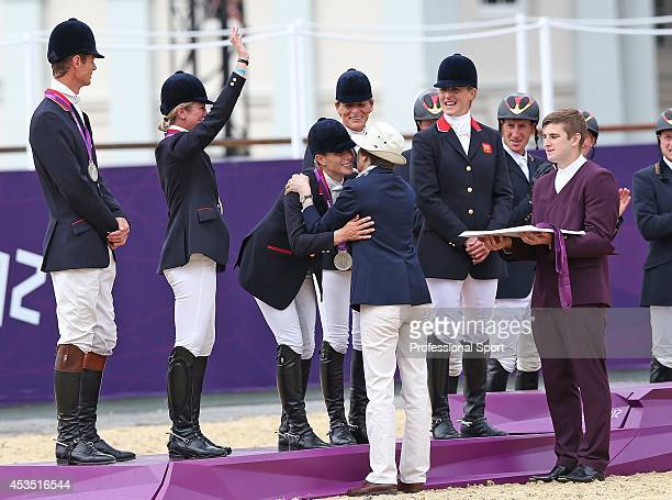 Princess Anne hugs her daughter Great Britain's Zara Phillips on the podium with her teammates after winning the silver medal in the team Equestrian...