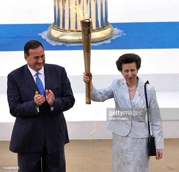Princess Anne, Princess Royal holds aloft the Olympic flame alongside Spiros Kapralos , President of Greek IOC at the Panathinaiko stadium during the...