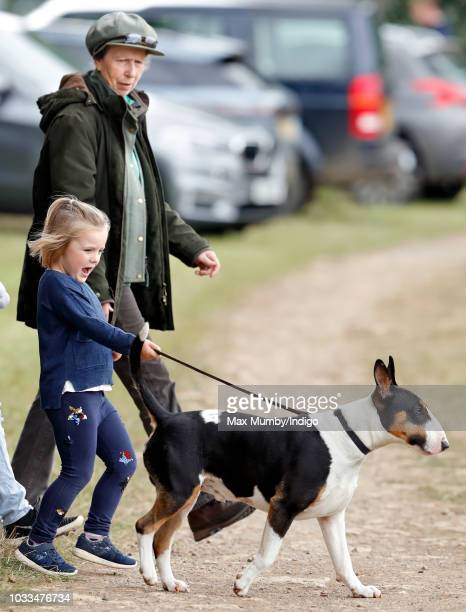 Princess Anne Princess Royal looks on as granddaughter Mia Tindall takes her bull terrier dog for a walk as they attend the Whatley Manor Horse...