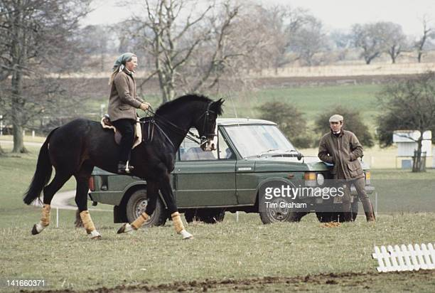 Princess Anne, the Princess Royal, and her husband Mark Phillips out riding at the Badminton Horse Trials in Gloucestershire, circa 1980. Anne is...