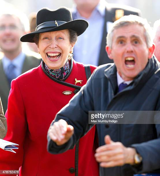 Princess Anne The Princess Royal watches the racing alongside a cheering racegoer as she attends Day 4 of the Cheltenham Festival at Cheltenham...