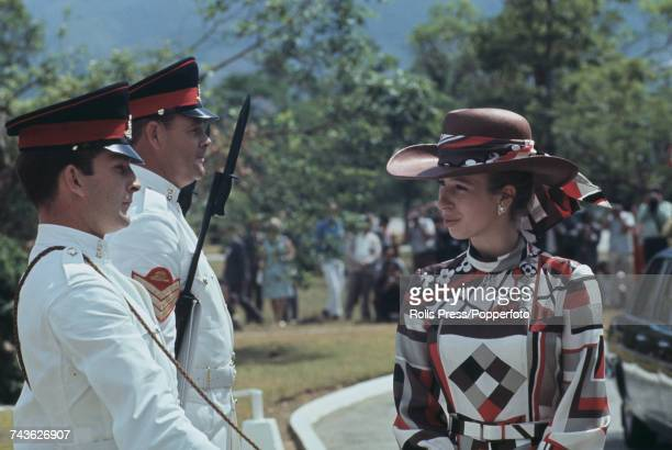 Princess Anne wearing a distinctive red brown and grey dress with matching hat inspects members of the Hong Kong Garrison part of British Forces...