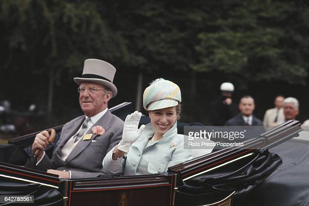 Princess Anne wearing a jockey cap pale blue jacket and white gloves waves to bystanders as she rides in a royal carriage to Ascot Racecourse during...