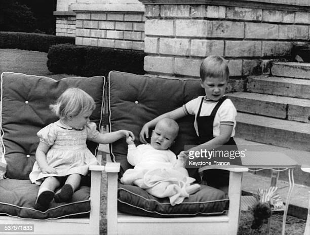 Princess Astrid, Prince Laurent and Prince Philip play on chairs in the park of the Belvedere castle on June 9, 1964 in Brussels, Belgium.