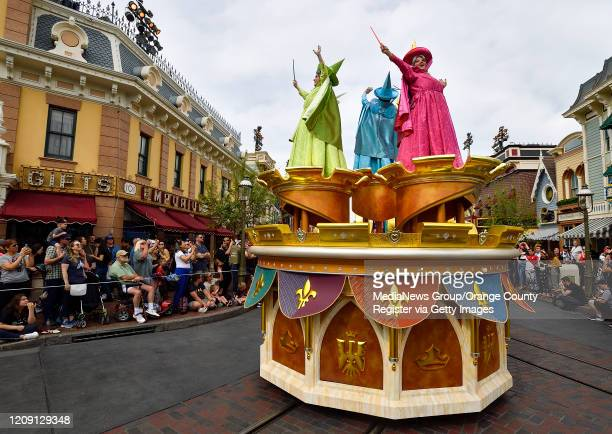 Princess Aurora's fairy godmothers, Flora, Fauna, and Merryweather, atop a float during the new Magic Happens Parade on Main Street U.S.A. Inside...