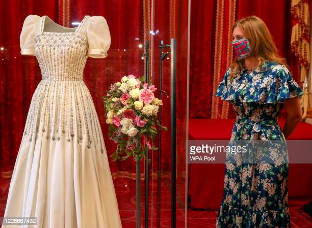 Princess Beatrice poses alongside her wedding dress as it goes on display at Windsor Castle on September 23, 2020 in Windsor, England. Princess...