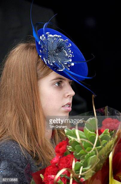 Princess Beatrice With Dental Brace To Correct Her Teeth Carrying Bouquets Of Flowers And Wearing A Hat With Feather Trim On Christmas Day