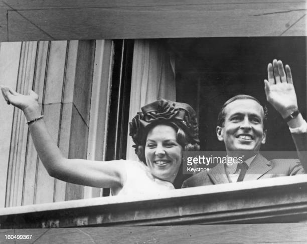 Princess Beatrix of the Netherlands and her fiancee Claus van Amsberg waving from a balcony during a visit to Amsterdam 6th July 1965