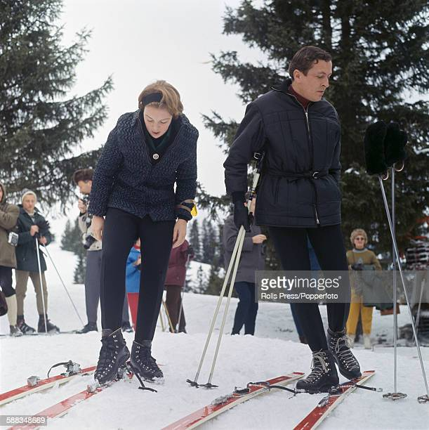 Princess Beatrix of the Netherlands pictured with her fiance Claus von Amsberg putting on skis as they prepare to descend the slopes at the resort of...
