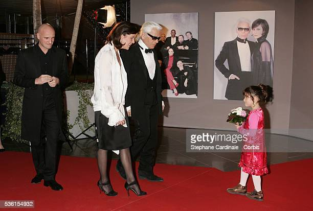 Princess Caroline of Hanover accompanied by Karl Lagerfeld and choreographer JeanChristophe Maillot receives a bouquet of flowers from a young girl...