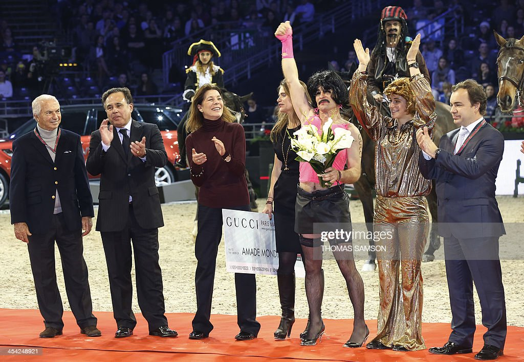Princess Caroline of Hanover (3rd L) congradulates the winners of the Style and Competition for Amade charity costumed event of the Paris Masters equestrian jumping competition, France's Thierry Rozier (3rd R) and Greece's Electra Niarchos (2nd R), on December 7, 2013 at the Parc des Expositions in Villepinte, north of Paris.