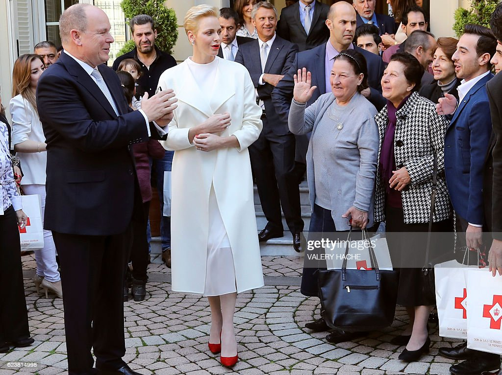 Princess Charlene (C) and Prince's Albert II (L) of Monaco leave after a family picture with refugees after giving them parcels at Red Cross headquarters' during the annual charity ceremony on November 17, 2016. Prince Albert II and Princess Charlene will attend several events before the Monaco National Day on November 19, in Monaco. / AFP / POOL / VALERY
