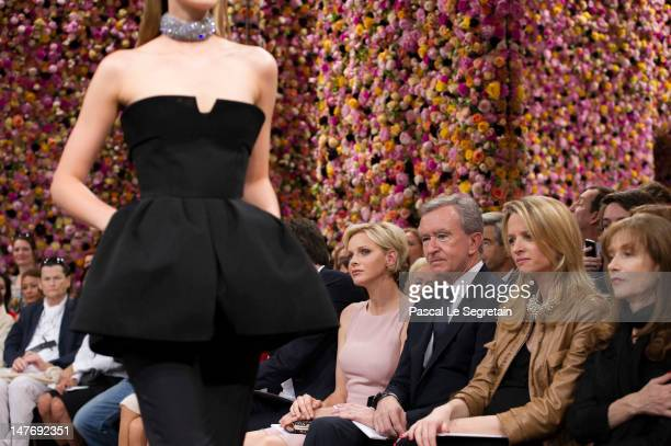 Princess Charlene, Bernard Arnault, Delphine Arnault and Isabelle Huppert look at a model during the Christian Dior Haute-Couture show as part of...